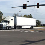 Semi and compact car driving through the intersection of 19th Street Court East and 44th Avenue East